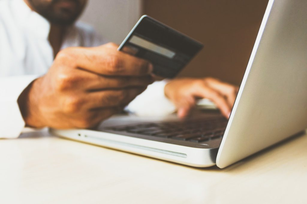 hand holding credit card in front of laptop symbolizing pci compliance