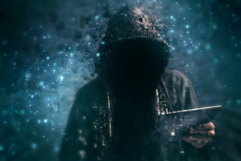 hacker in a dark hoodie holds a tablet surrounded by glitchy pixels